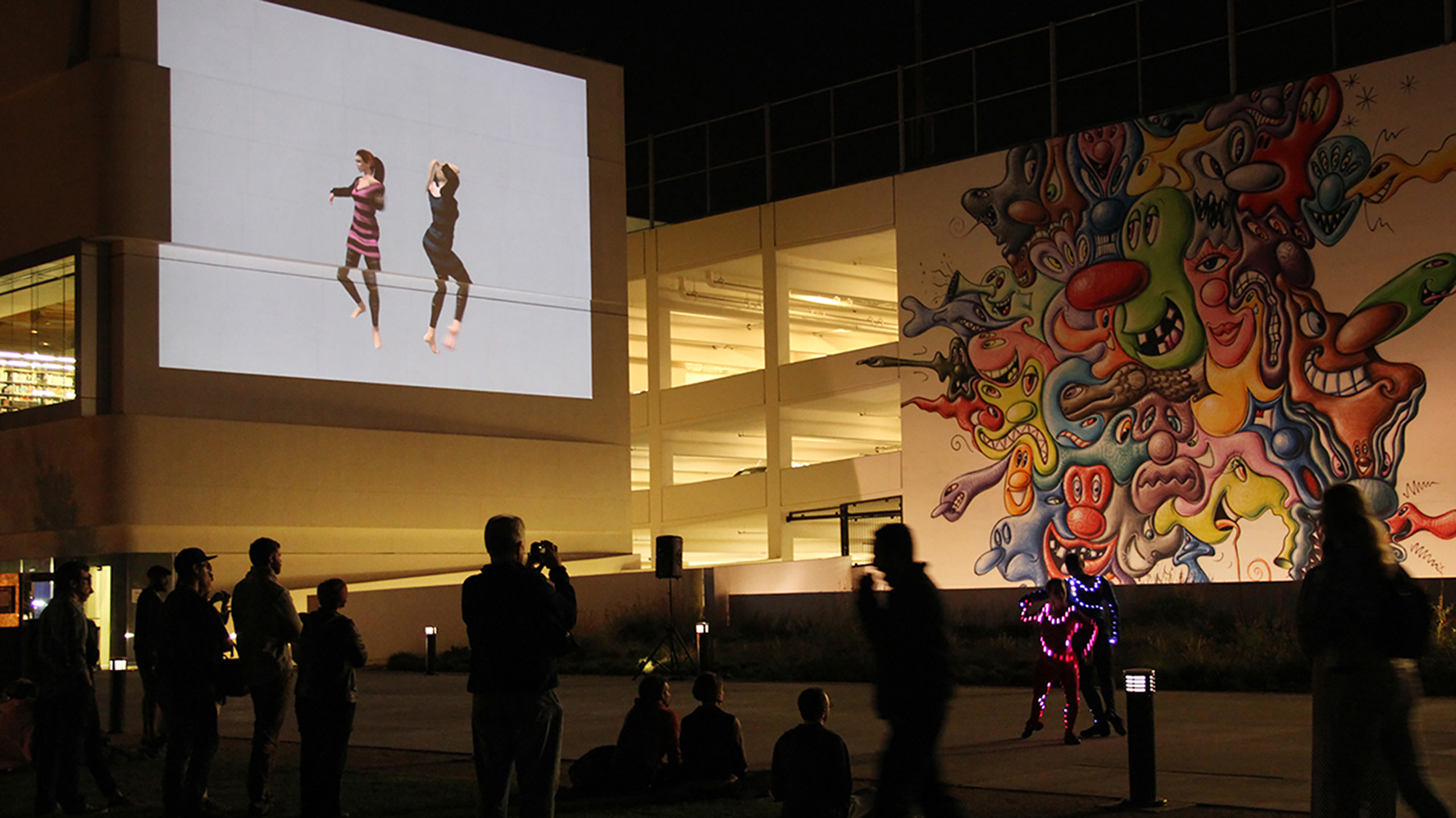 Vanessa Blaylock Company dancers projected onto a large parking structure wall as Donna Sternberg Dancers perform on the ground at ONE NIght