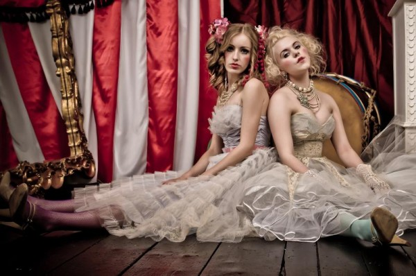 two women, sitting on the floor, back to back, in fancy, frilly party dresses