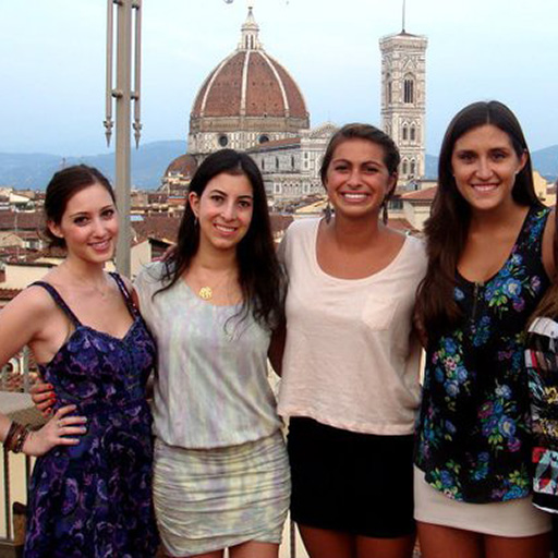 4 women on a balcony in Florence, Italy, with The Basilica di Santa Maria del Fiore in the distance.