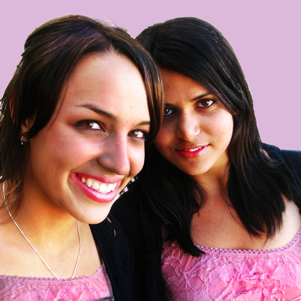 two friends in pink dresses smiling and looking at the camera
