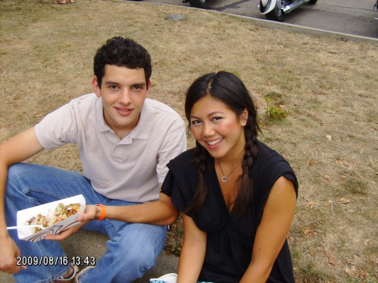 Friends List: Two young friends, a girl in black, and a guy in white, sitting on the grass, smiling, and eating taquitos