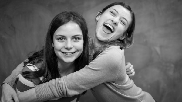 Friends List: black-and-white photo of 2 young girls laughing, smiling, and embracing each other