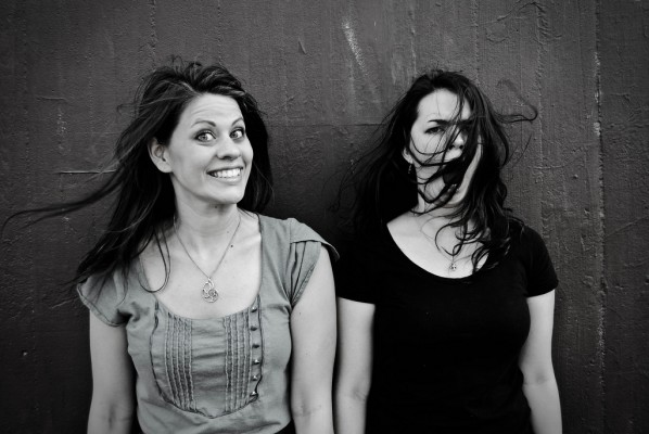 black and white photo of two women against a wall. One is smiling and looking at the camera, the other is yawning with the wind blowing her long, dark hair into her face