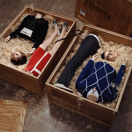 """Hugh Kretschmer's 2006 photograph """"Special Delivery"""" depicting 2 people in parts in shipping crates and wearing stylish apparel."""