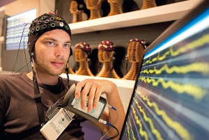 Image of a man wearing a cap of electrodes and looking at his brain activity on a monitor