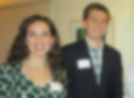 out-of-focus color photograph of a woman in a dress and a man in a suit looking at the camera
