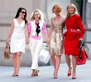 the 4 lead characters of Sex and the City walking down the street in New York City and holding hands
