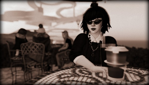 Photo of Vanessa Blaylock sitting at a tile topped table drinking a latte at Bacon Barista on a dusky Medici University morning