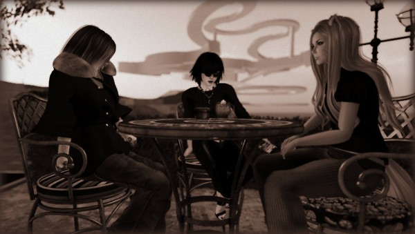 Scarlett Luv-Star, Vanessa Blaylock, and Emma Maybe sit at a tile-topped table on a terrace at Bacon Barista having coffee on a dusky  morning