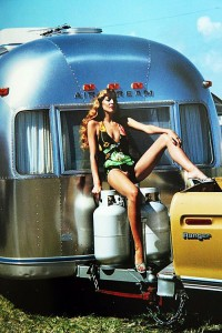 Shiny, sparkling, silver Airstream hitched to an unidentified vehilcle and with a very beach ready FIona Blaylock in a swimsuit and sitting on top of the Airstream's propane tanks.