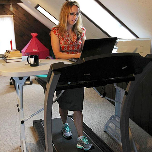 """Building a treadmill desk: Dr. Sherry Pagoto on a treadmill desk she built at home by placing a """"Trek Desk"""" over a treadmill she already had and then using her laptop and other materials on the Trek Desk."""
