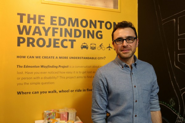 University Guiding Principles: photo of a man standing in front of an informational sign for the Edmonton Wayfinding Project
