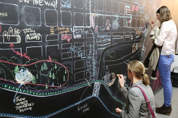 University Guiding Principles: photo of the Edmonton Wayfinding Project featuring people annotating the city on a chalk board