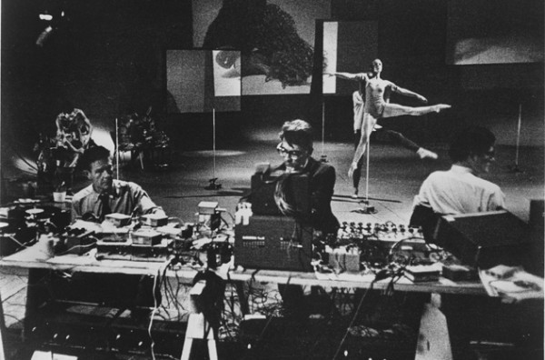 Indeterminacy: a black and white photograph of John Cage, other artists, and dancers, working on Variations 13