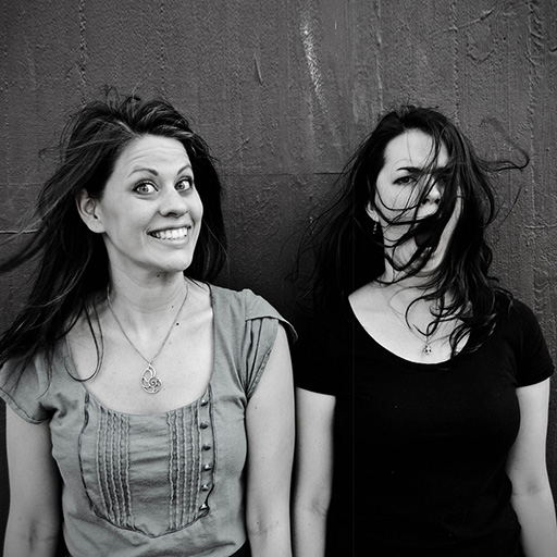 black-and-white photo of 2 women standing side by side and against a wall. One has a big smile when the wind blows the other's hair.