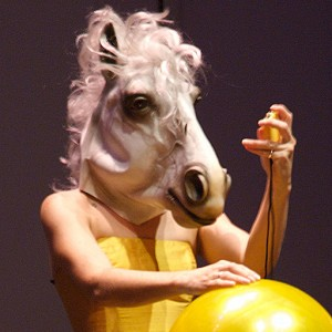 Micol Hebron in a yellow dress and wearing a horse head mask