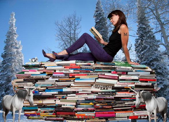 Micol Hebron seated on top of a giant pile of art and theory books. She relaxes and reads a book.