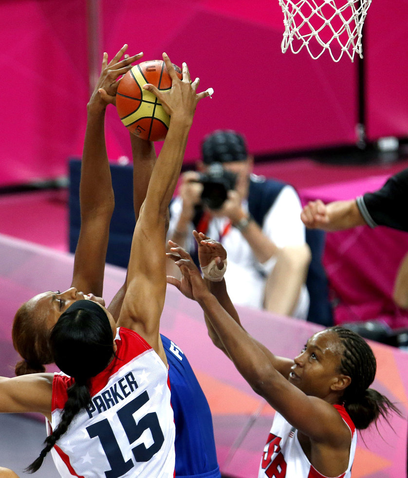 Women's basketball players leaping high with hands on opposite sides of a basketball and the net less than a meter away