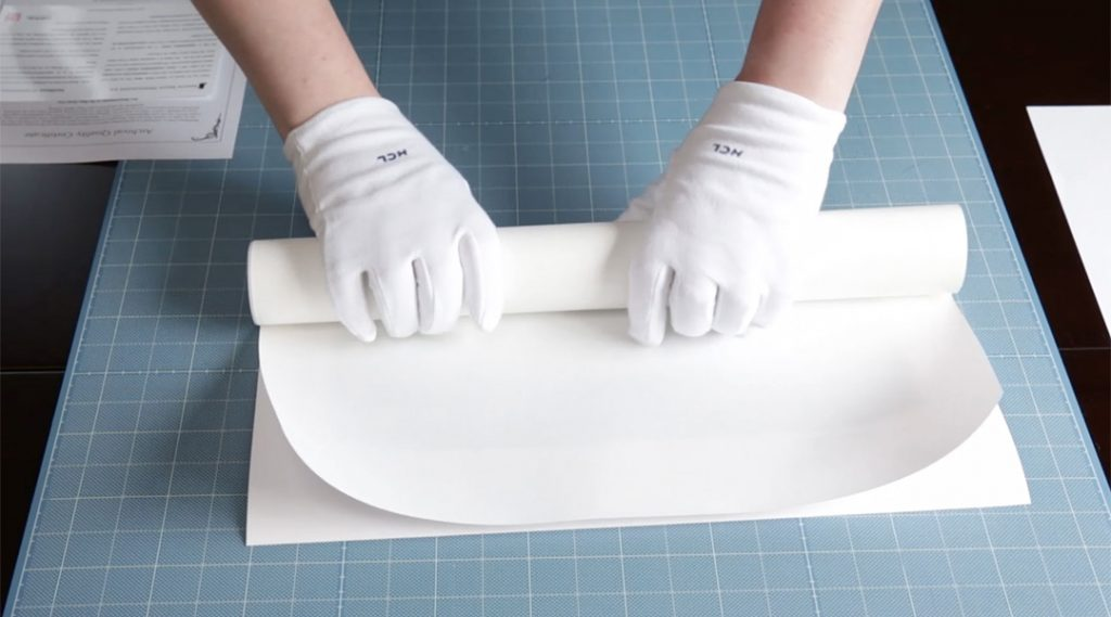 photograph of hands wearing cotton gloves and rolling up a fine print